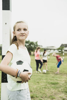 Portrait of smiling teenage girl with soccer ball leaning at goalpost - UUF001553