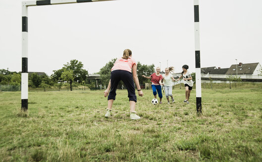 Four teenage girls playing soccer on a football ground - UUF001554