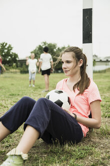 Portrait of smiling teenage girl with soccer ball leaning at goalpost - UUF001559