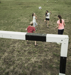 Four female teenage friends playing soccer, elevated view - UUF001561