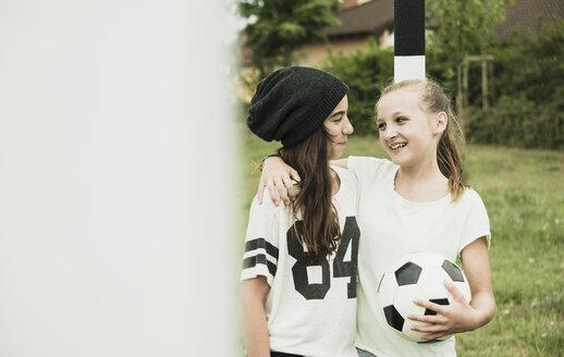 Two happy teenage girls standing on a football ground - UUF001567