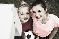 Two smiling teenage girls standing side by side on a football ground, elevated view - UUF001572