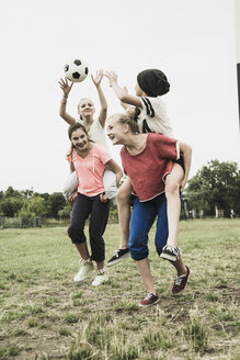 Four teenage girls having fun on a soccer field - UUF001575