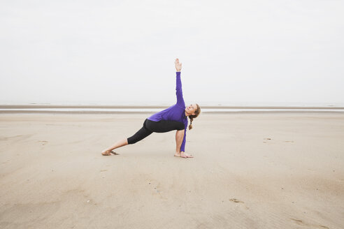 Belgium, Flanders, woman doing yoga exercises on the beach - GW003705