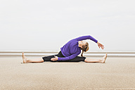 Belgium, Flanders, woman doing yoga exercises on the beach - GW003710