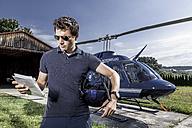 Germany, Bavaria, Landshut, Helicopter pilot holding map - KDF000059