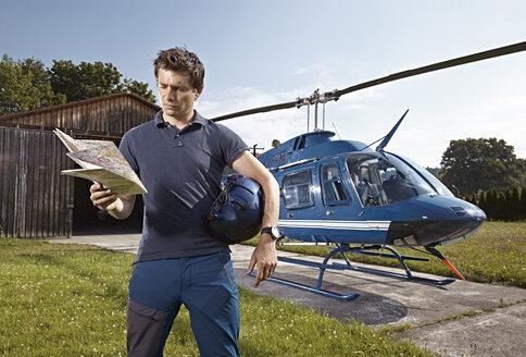 Germany, Bavaria, Landshut, Helicopter pilot holding map - KDF000060
