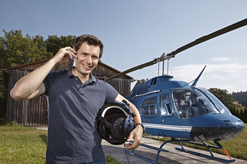 Germany, Bavaria, Landshut, Helicopter pilot using mobile phone - KDF000065