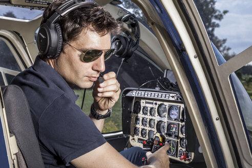 Germany, Bavaria, Landshut, Helicopter pilot in cockpit - KDF000038