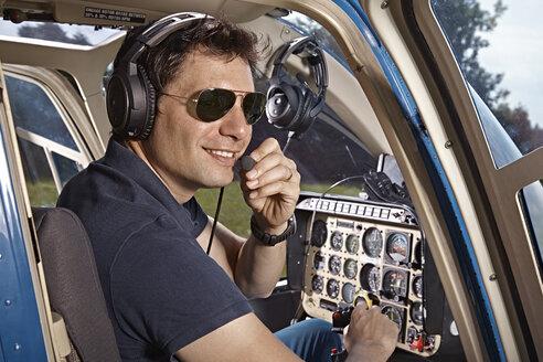 Germany, Bavaria, Landshut, Helicopter pilot in cockpit - KDF000039