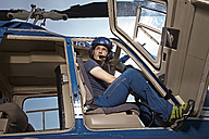 Germany, Bavaria, Landshut, Helicopter pilot sitting in open helicopter, waiting - KDF000070