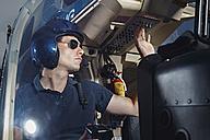 Germany, Bavaria, Landshut, Helicopter pilot in cockpit - KDF000043