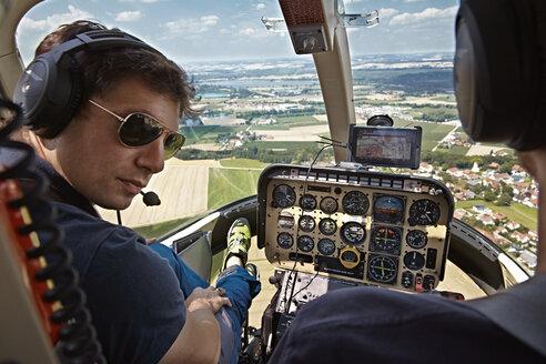 Germany, Bavaria, Landshut, Helicopter pilot in cockpit - KD000046