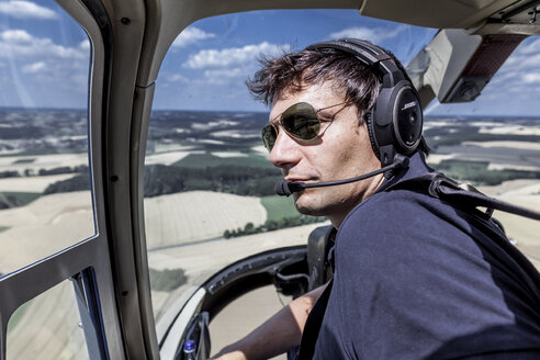 Germany, Bavaria, Landshut, Helicopter pilot in cockpit - KDF000048
