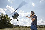 Germany, Bavaria, Landshut, Air traffic controller securing landing and take off of helicopoter - KDF000049