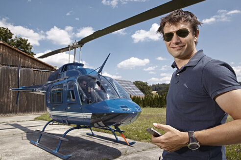 Germany, Bavaria, Landshut, Helicopter pilot checking mobile phone - KD000057