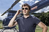 Germany, Bavaria, Landshut, Helicopter pilot using mobile phone - KDF000087
