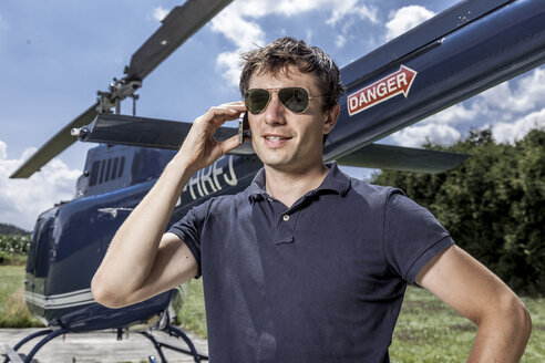 Germany, Bavaria, Landshut, Helicopter pilot using mobile phone - KDF000087