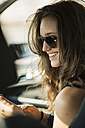 Portrait of smiling teenage girl with sunglasses sitting in a car using her smartphone - UUF001593