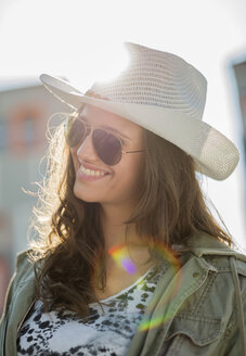 Portrait of smiling teenage girl wearing sunglasses and white hat - UUF001595