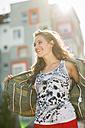 Portrait of smiling teenage girl taking off her jacket - UUF001626