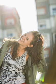 Portrait of laughing teenage girl with hand in her hair - UUF001649