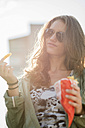 Portrait of teenage girl wearing sunglasses holding paperbag of French Fries - UUF001628
