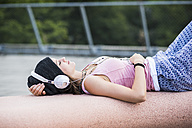 Smiling teenage girl with closed eyes hearing music with headphones - UUF001602