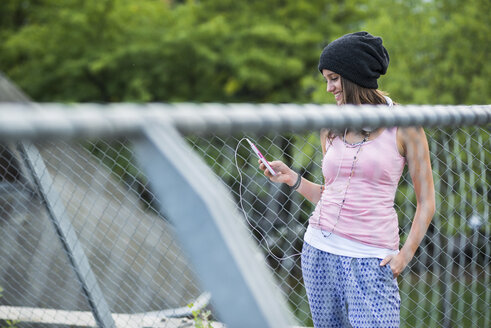 Smiling teenage girl standing behind a wire fence using smartphone - UUF001634