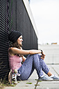 Smiling teenage girl with skateboard sitting in front of a black facade - UUF001608