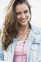 Portrait of smiling teenage girl wearing jeans jacket - UUF001639