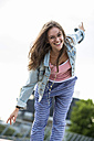 Portrait of smiling teenage girl balancing with outstretched arms - UUF001611