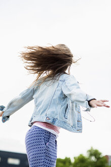 Teenage girl wearing jeans jacket jumping into the air, back view - UUF001612