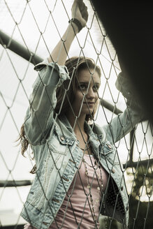 Portrait of teenage girl standing behind a wire fence - UUF001615