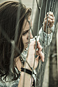 Teenage girl looking through a wire fence - UUF001616