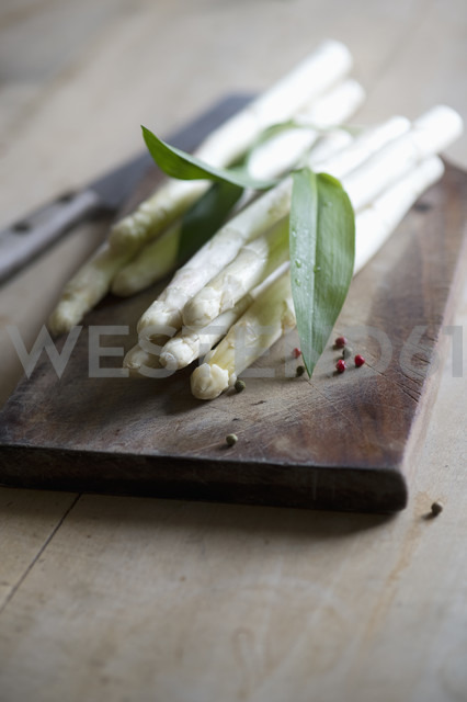 Fresh white asparagus and ramson leaves on chopping board - ASF005461