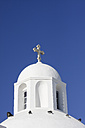 Greece, Cyclades, Santorini, cupola with cruzifix of a white church in front of blue sky - KRPF000850