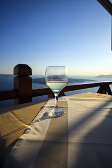 Greece, Cyclades, Santorini, wine glass standing on a table at evening twilight - KRPF000854