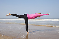 Belgium, Flanders, woman doing yoga exercise on the beach - GW003528