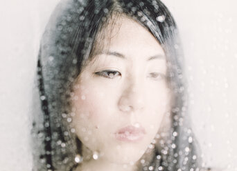 Young woman looking through a window with water drops - FLF000477