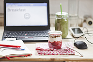 Green smoothie and yogurt breakfast on desk with laptop - SBDF001199