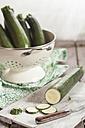 Colander of courgettes and a knife and slices of courgettes on chopping board - SBDF001215