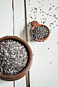 Earthenware dish and wooden spoon of organic black chia, Salvia hispanica, on white wood - SBDF001163