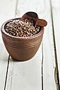 Earthenware dish of organic linseed, Linum usitatissimum, on white wood - SBDF001166