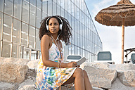 Young woman with headphones and digital tablet outdoors - KD000392