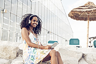 Happy young woman with headphones and digital tablet outdoors - KD000394