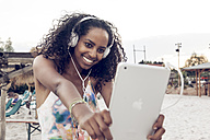 Happy young woman with headphones and digital tablet outdoors - KD000400