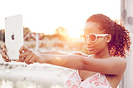 Young woman taking selfie with digital tablet at sunset - KD000472