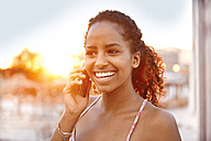 Happy young woman on cell phone at sunset - KD000474