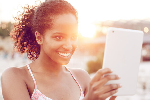 Happy young woman with digital tablet at sunset - KD000418